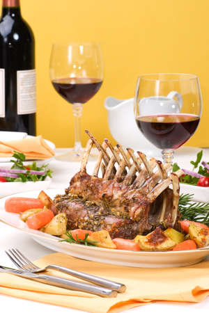 Rack of Lamb (ribs) with Rosemary garlic dressing, garnished with  carrots, potatoes and rosemary sprigs. Dinner settigns.