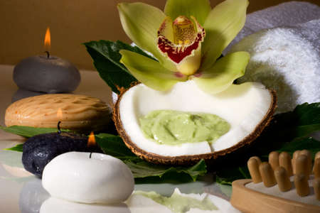 scrub: Avocado coconut scrub in coconut shell, orchid flower (Cymbidium sp.) and candles. Suited for relaxing and health commercials Stock Photo