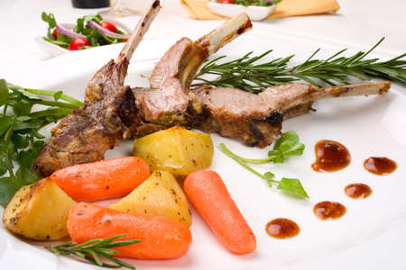 Lamb chops (ribs) with Rosemary garlic dressing, garnished with  carrots, potatoes and rosemary sprigs. Dinner settings. Stock Photo - 2459442