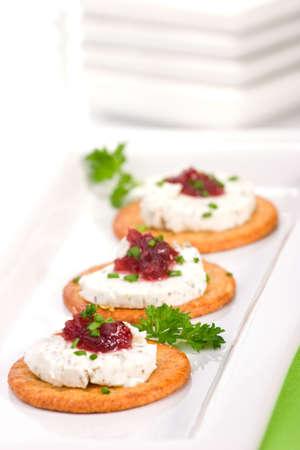 sandwiche: Tre crackers con formaggio di capra e salsa di mirtilli arancione in vacanza tabella.