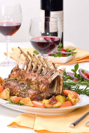 Rack of Lamb (ribs) with Rosemary garlic dressing, garnished with  carrots, potatoes and rosemary sprigs. photo
