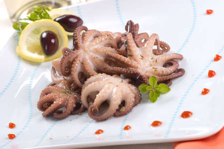 black octopus: Closeup of delicious octopus cooked in red wine sauce, lemon slices and olives Stock Photo