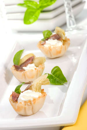 Three mini fillo shells filled with cream cheese, marinated artichoke, anchovy and basil on holiday table