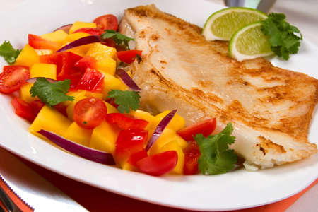 red onion: Closeup of fried skate (ray) with mango, cherry tomato and red onion salsa.  Stock Photo