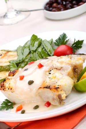 alcaparras: Fletán asado con alcaparras y pimienta servido con salsa de calabacín asado, limón, lima, tomate. guisantes verdes y vaso de vino blanco  Foto de archivo