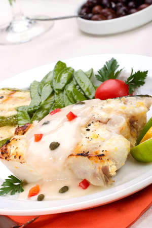capers: Grilled halibut with capers and pepper sauce served with grilled zucchini, lemon, lime, tomatoes. green peas and glass of white wine Stock Photo
