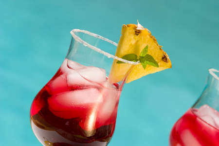 Glass of summer cranberry alcohol cocktail on swimming pool side outside of hotel in hot day, suited for vacation or travel theme Stock Photo