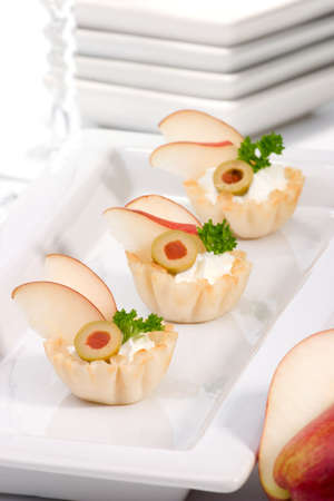 Three mini fillo shells filled with cream cheese, pears, olives and parsley on holiday table Imagens