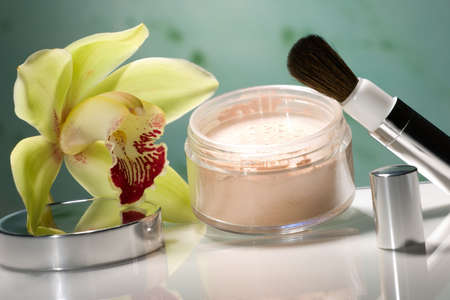 talcum: Closeup of container of opened face powder, brush and blooming yellow orchid flower on reflected surface