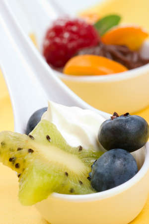 Closeup of a la carte spoon filled with delicious vanilla souffle  served with fresh kiwi and blueberry photo
