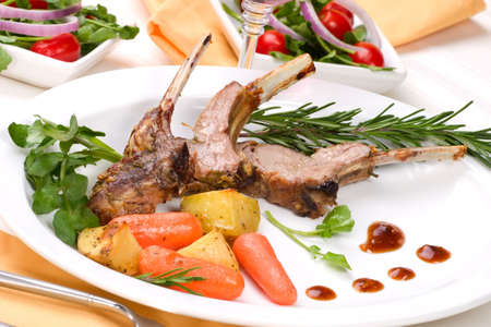 Lamb chops (ribs) with Rosemary garlic dressing, garnished with  carrots, potatoes and rosemary sprigs. Dinner settings. Stock Photo