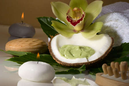 Avocado coconut scrub in coconut, orchid flower (Cymbidium sp.) and candles. Suited for relaxing and health commercials photo