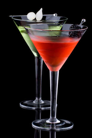 chilled: Classical martini in chilled glass over black background on reflection surface, garnished with freah blackberry and marinated pearl onoions. Most popular cocktails series. Stock Photo