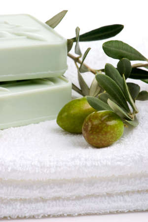 natural soap: Spa set - fresh green olives and organic soap over white towel. best suited for relaxing and health commercials Stock Photo