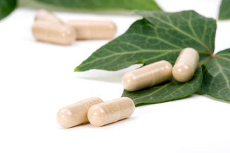 Closeup of herbal supplement pills and fresh ivy leaves best suited for alternative medicine ads. Shallow DOF. Imagens
