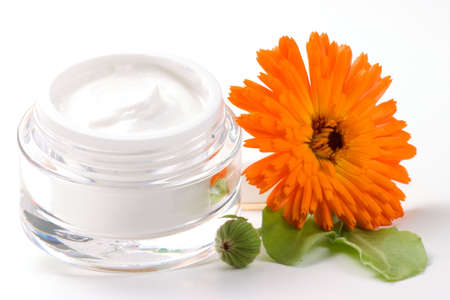 Closeup of jar of moisturizing face cream and fresh marigold flower