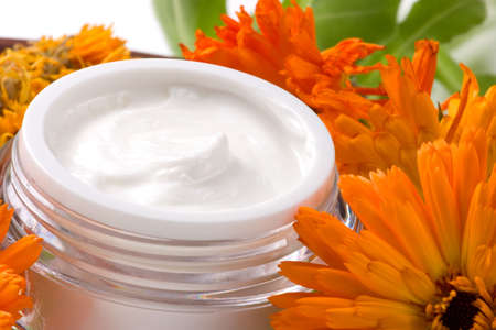 Closeup of jar of moisturizing face cream surrounded by fresh and dried marigold flowers Stock Photo