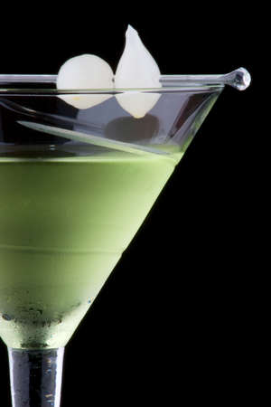 vermouth: Kyoto cocktail in chilled martini glass over black background on reflection surface. Green color, gin, dry vermouth, melon liqueur,  garnished with marinated pearl onions. Most popular cocktails series. Stock Photo
