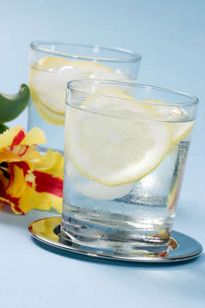 Closeup of chilled glasses of fresh water with sliced lemon and ice cubes over aqua paper background photo