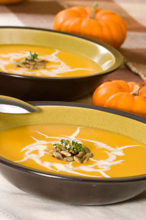 Two bowls of hot delicious pumpkin soup garnished with cream, roasted pumpkin seeds and fresh thyme Stock Photo - 2911420