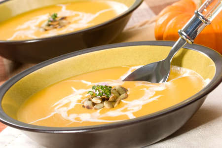Two bowls of hot delicious pumpkin soup garnished with cream, roasted pumpkin seeds and fresh thyme Stock Photo