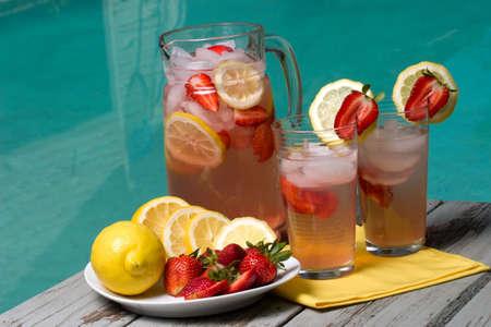 limonada: Dos cristales del hogar hicieron la limonada y la jarra rosadas fr�as heladas de la fresa en verano caliente en el borde de la piscina.