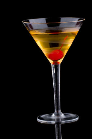 French martini in chilled glass over black background on reflection surface, garnished with maraschino cherry.
