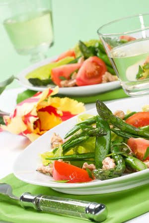 Two plates of asparagus, snow pea and tomato salad with ginger dressing. Glass of white wine and spring tulip photo