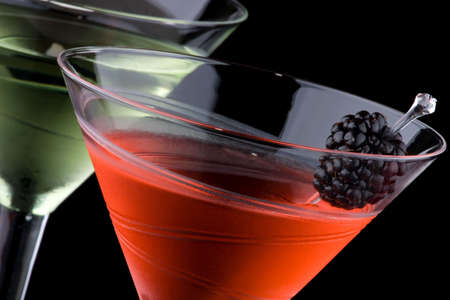 chilled: Classical martini in chilled glass over black background on reflection surface, garnished with fresh blackberry and marinated pearl onions. Most popular cocktails series. Stock Photo