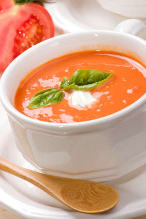 Closeup of bowls of delicious tomato soup garnished with cream and basil leaves