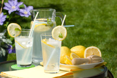 Two glasses of home made iced cold lemonade and pitcher on hot summer. Copyspace photo