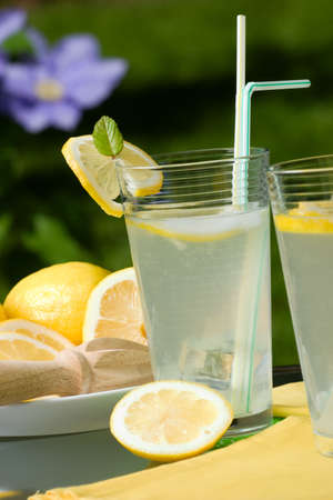 Closeup of glass of home made iced cold lemonade and plate of lemon slices on hot summer day.  photo