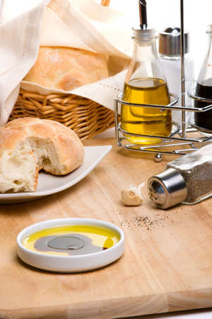 Pepper pot with black pepper, fresh bread, bottle of olive oil and spicy herbs on wooden cut board photo