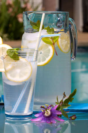 Two glasses of home made iced cold lemonade and pitcher on hot summer on edge of swimming pool.  版權商用圖片