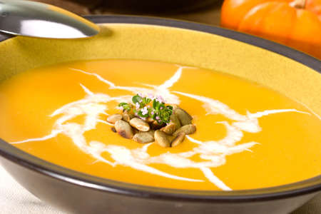 Closeup of bowl of hot delicious pumpkin soup garnished with cream, roasted pumpkin seeds and fresh thyme Stock Photo - 3221453