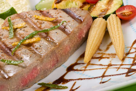 Closeup of juicy delicious Citrus-peppercorn-spiked grilled tuna steak with grilled vegetables.  photo