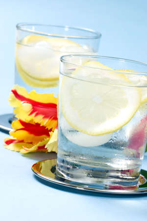 flux: Closeup of chilled glasses of fresh water with sliced lemon and ice cubes over aqua paper background Stock Photo