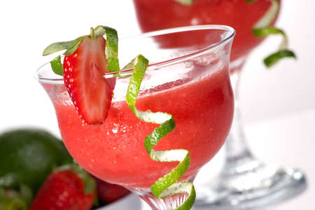 Strawberry Daiquiri cocktails. Rum, strawberries, liqueur, lime juice garnished with strawberry and twist of lime. Fresh strawberries and lime around. Most popular cocktails series.