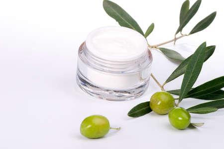 cremas faciales: Closeup de tarro de crema hidratante cara y ramita con aceitunas verdes.