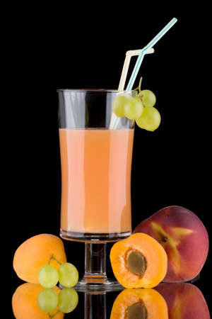 Organic juice made from apricots, grapes and peaches surrounded by fresh fruits. Series about organic and healthy drinks. photo