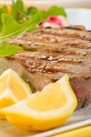 Closeup of juicy delicious Citrus-peppercorn-spiked grilled tuna steak with grilled vegetables. Shallow DOF photo