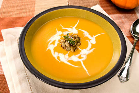Bowl of hot delicious pumpkin soup garnished with cream, roasted pumpkin seeds and fresh thyme Stock Photo - 3417781