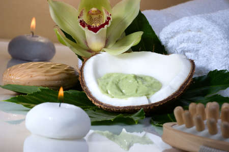 Avocado coconut scrub in coconut shell, orchid flower (Cymbidium sp.) and candles. Suited for relaxing and health commercials photo