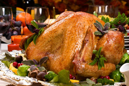 Garnished roasted turkey on holiday decorated table with pumpkins and glasses of red wine Stock Photo - 3417782