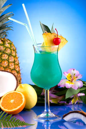 blue hawaiian drink: Blue Hawaiian cocktail surrounded by tropical fruits. Rum, pineapple juice, coconut milk and blue curacao garnished with slice of pineapple and maraschino cherry. Most popular cocktails series.