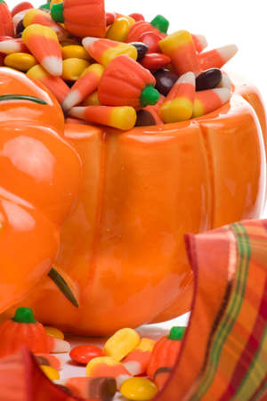 Closeup of pumpkin filled with delicious Halloween candy over fall leaves background photo