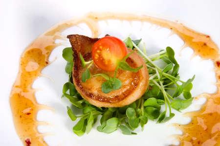 Closeup van Ginger Soy Coquilles omwikkeld met bacon gegarneerd met verse cherrytomaatjes en daikon spruitjes.