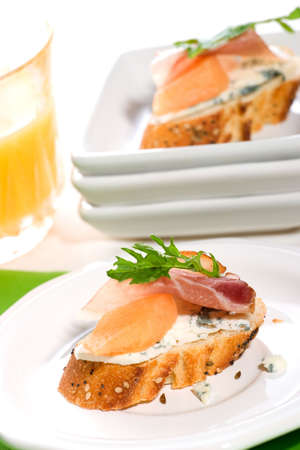 Closeup of two delicious Prosciutto canapes-sandwiches made from cantaloup melon, blue cheese, Prosciutto ham and salad. Orange juice. photo