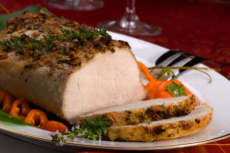 redwine: Delicious sliced garlic thyme roast pork loin and glass of red wine ready for Christmas dinner on holiday table.