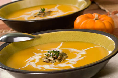 Closeup of bowl of hot delicious pumpkin soup garnished with cream, roasted pumpkin seeds and fresh thyme Stock Photo - 3534852
